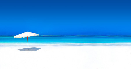 Wall Mural - Parasol on white beach with turquoise ocean and cloudless sky