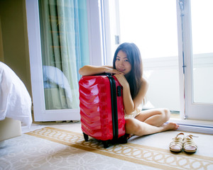 lifestyle natural portrait of young happy and beautiful Asian Korean tourist woman with travel suitcase arriving tired at five star hotel sitting at room floor
