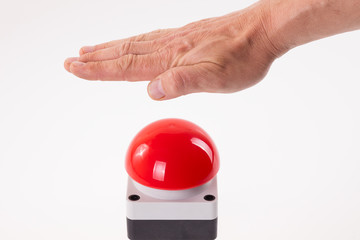 Hand pushing a red buzzer