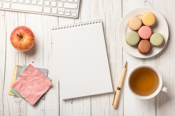 Office desk with tea and macaroons