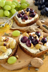Crostini with roasted grapes, goat cheese, walnuts and honey, vertical