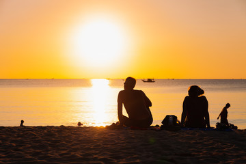Silhouette of people sit on the beach and enjoying the sunset.
