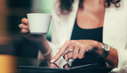 Woman having coffee and using tablet