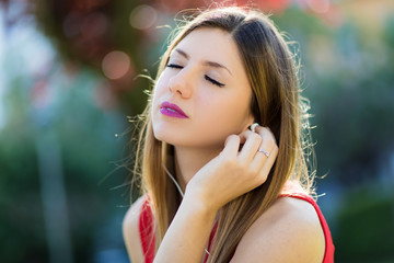Woman listening to music sitting ona bench in a park in a hot summer sunny day
