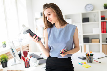 Beautiful Young girl in the office is standing near the table, holding glasses in her hand and looking at the phone screen.