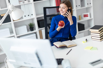 A young girl is sitting at a computer desk, holding an apple in her hand and talking on the phone. Before the girl lies an open book.