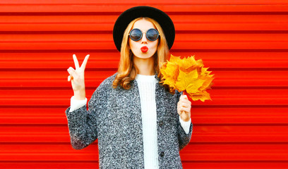 Funny cool girl with red lips and yellow maple leaves on a background