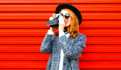 Happy pretty woman holds retro camera on a red background