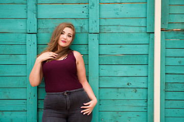 Beautiful woman wearing ripped jeans standing against cafe wall on city street. Casual fashion, elegant everyday look. Plus size model.