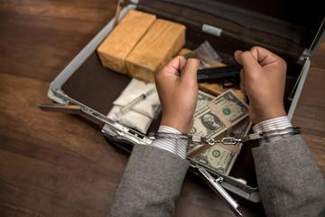 Cocaine, marijuana dollars and handgun on wooden table