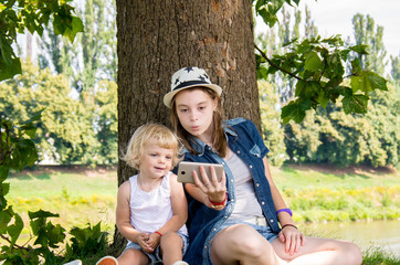 two happy sisters do selfie in the nature of a tree