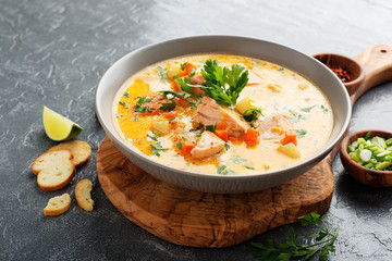 Salmon soup with cream, potatoes, carrots and parsley on gray background.