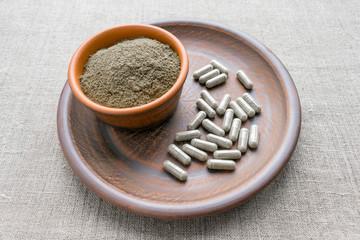 Triphala capsules and powder on clay plate. Triphala is polyherbal Ayurvedic medicine of Indian gooseberry or amalaki; baheda or bibhitaki; and chebulic myrobalan or haritaki