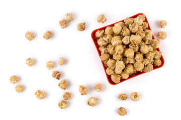 Caramel popcorn in a quadratic red plate, isolated on white background