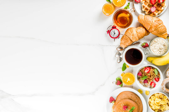 Healthy breakfast eating concept, various morning food - pancakes, waffles, croissant oatmeal sandwich and granola with yogurt, fruit, berries, coffee, tea, orange juice, white background