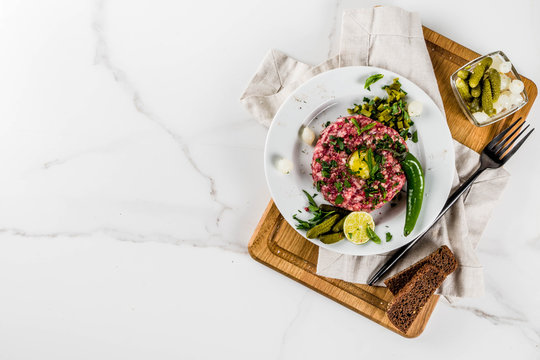 French cuisine, beef steak tartare with raw quail egg yolk, pickled cucumber and onions, fresh herbs, bread, white marble background copy space above