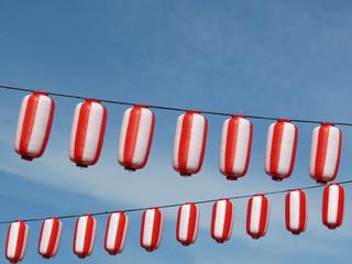 Red-white japanese paper lanterns Chochin on blue sky background