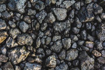 Texture of gray sharp uneven stones, illuminated by the morning sun