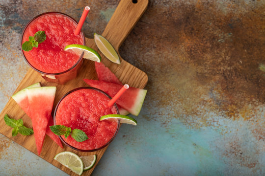 Watermelon slushie with lime, summer refreshing drink in tall glasses on a blue rusty background. Top view with copy space