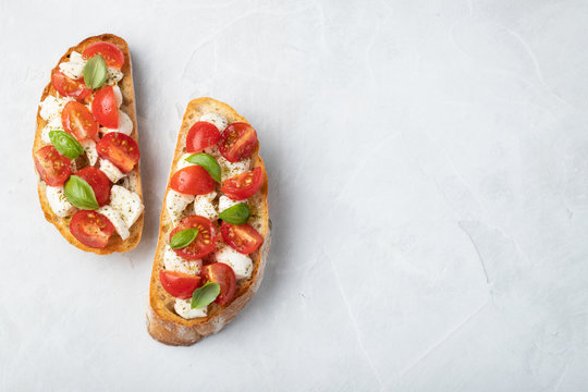 Bruschetta with tomatoes, mozzarella cheese and basil on a light background. Traditional italian appetizer or snack, antipasto. Top view with copy space. Flat lay