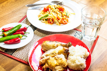 A traditional Thai meal of  papaya salad (som tam) with roast chicken, sticky rice, chillies and water