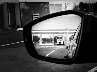Car rear view mirror with reflection of white truck filling gas at the gas station - black and white image