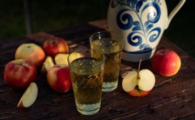 Traditional apple wine in the city of Frankfurt in Hesse. A jug of wine is on an old wooden table in the garden, around it are apples