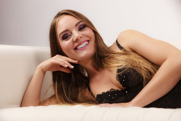 Woman lying in black lace lingerie on couch