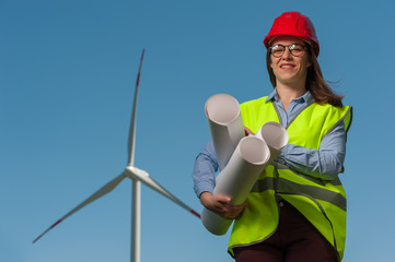 Portrait of a serious cute young female engineer in a green waistcoat and red hard hat with geodesic plans in hand against the backdrop of a windmill and blue sky.