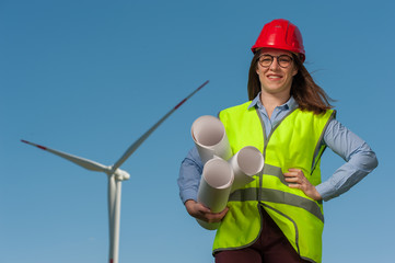 Positive young female engineer in red helmet and glasses with projects and plans against the background of a windmill and blue sky