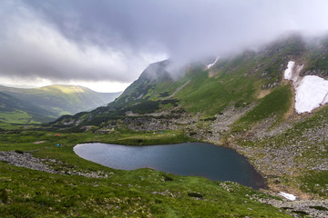 Fantastic wide peaceful view of blue lake in green valley and small tourist tents at rocky mountain with patches of snow covered with low clouds. Beauty of nature, tourism and traveling concept.
