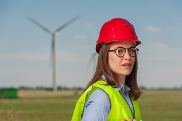 Portrait of a beautiful young female engineer in red helmet and glasses against the background of a windmill and blue sky