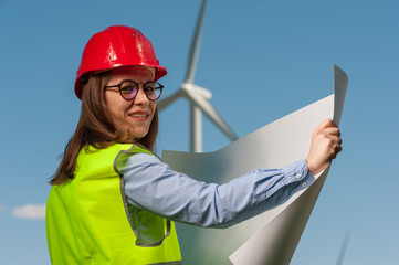 Beautiful young woman engineer looking at a plan of repair work on the background of a windmill