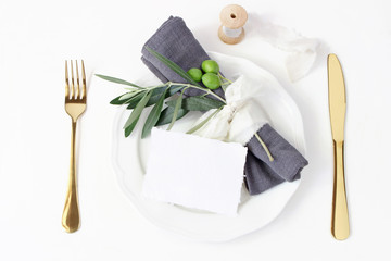 Festive table summer setting. Golden cutlery, olive branch, linen napkin, porcelain dinner plate and silk ribbon on white table background. Blank card mockup. Mediterranean wedding or restaurant menu