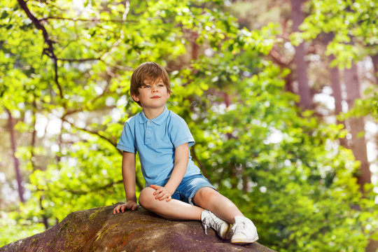 Little boy sit on stone in the forest