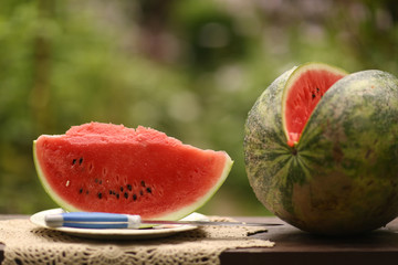 cut ripe big water melon still life with knife on green garden background close up photo