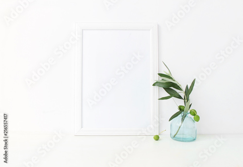 White Vertical Blank Wooden Frame Mockup With A Green Olive Branches In Blue Glass Vase Lying