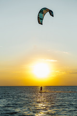 professional kiter doing a complicated trick on a beautiful sunset background