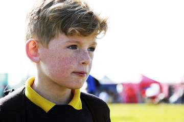 Boy with carnival tents behind him