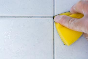 Reinigung von verschimmelten und verdreckten Fugen im Bad mit einem Schwamm