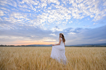 Beautiful woman in a field of rye at sunset. A woman in amazing clothes walking through the field of rye.