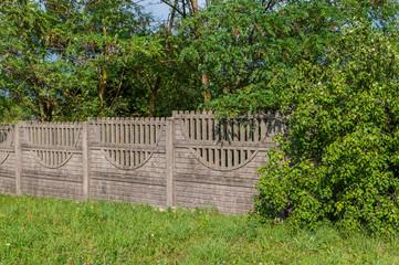 Betonowe ogrodzenie i zielone drzewa