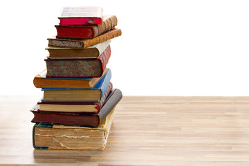 Tower of vintage books with open one on wooden shelf over white background