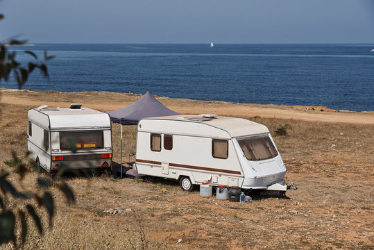 The house on wheels is parked on the beach in front of the blue sea in the wild