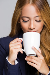 Asian businesswoman having coffee.