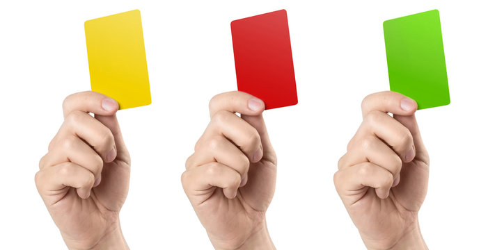 Male football (soccer) referee hand holding yellow, red and green cards, isolated on white background