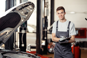 A qualified automechanic is at his work while checking an automo