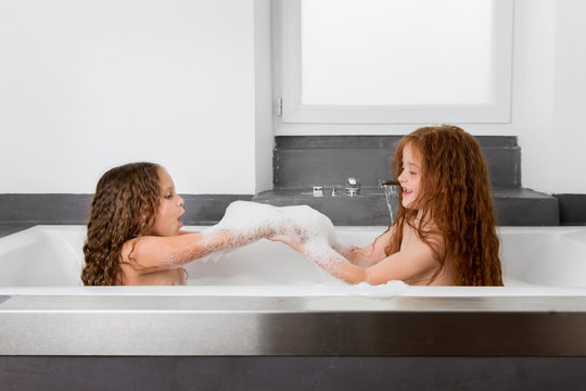Little girls in soapy bubble bath playing with suds