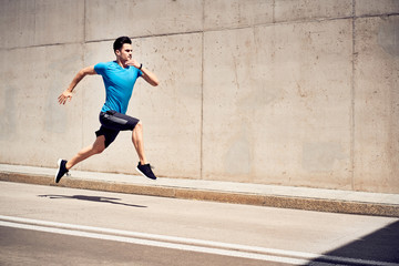 Health and fitness concept. Man doing sprinting and jumping exercises during workout session in the city