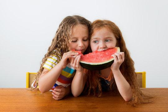 Little girls sharing a slice of watermelon